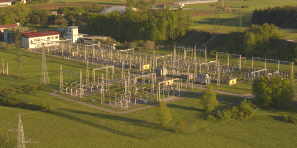 AERIAL: High voltage power line towers and electricity power plant in suburbs
